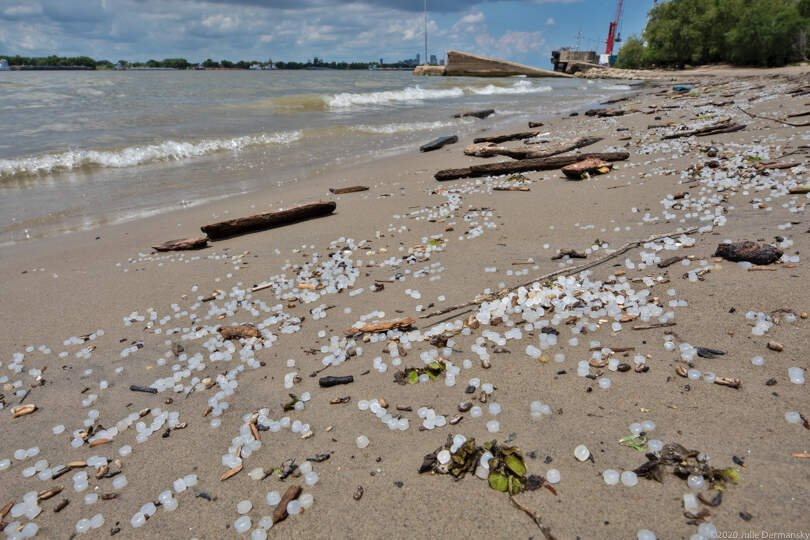 Plastic nurdles scattered on a beach along the Mississippi